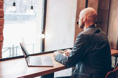 Thinking attractive adult successful bald bearded man in suit with laptop in cafe stock images