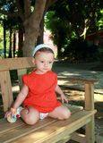 Thinking baby girl sitting on bench Stock Images
