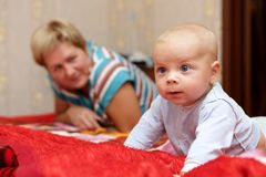 Thinking baby with his grandmother stock image