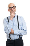 Thinking bald man with suspenders and bow-tie looking up Stock Photo