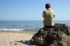 Thinking at beach. Beach, rock and alone man. Alone man thinking at the beach stock image
