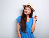 Thinking beautiful woman in hat and blue top looking up on blue Stock Images