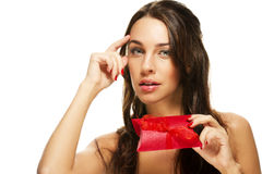 Thinking beautiful woman holding red present Royalty Free Stock Photo
