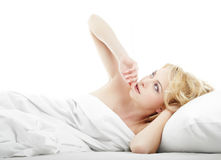 Thinking on the bed. Serene lady thinking and laying on the bed Royalty Free Stock Photography