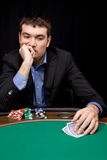 Thinking before bet in casino. Stylish man in black suit thinking before bet in the casino Royalty Free Stock Image