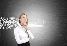 Thinking blond woman and tangled arrows Royalty Free Stock Images