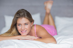 Thinking blonde lying on her bed smiling Royalty Free Stock Photography