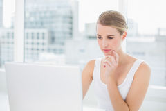 Thinking blonde using her laptop Stock Photography