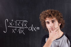 Thinking boy with blackboard solving equation Royalty Free Stock Images