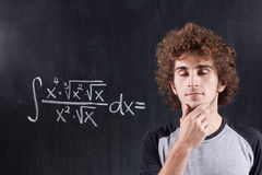 Thinking boy with blackboard solving equation Stock Images