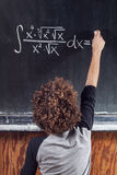 Thinking boy with blackboard solving equation Royalty Free Stock Image