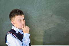 Thinking boy at the chalkboard Royalty Free Stock Image