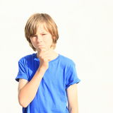 Thinking boy. Face of a thinking little boy in blue t-shirt Royalty Free Stock Photo