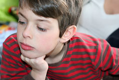 Thinking boy with hand under chin. A thinking boy with right hand under his chin Royalty Free Stock Images
