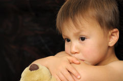 Thinking boy hugging teddy bear Stock Images
