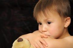 Thinking boy hugging teddy bear Stock Images