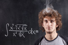 Thinking boy solving equation with smoking head Stock Photo