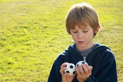Thinking boy with two balls. Face of a little boy being thinking over two football balls royalty free stock photos