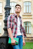 Thinking about a bright future. Low angle view of thoughtful male student holding book and looking up while standing against university building Royalty Free Stock Photography