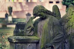 Thinking broody angel statue on Malostransky cemetery, Prague, Czech Republic. Contemplative angel statue with laurel wreath on Malostransky cemetery, Prague Royalty Free Stock Image