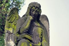 Thinking broody angel statue on Malostransky cemetery, Prague, Czech Republic. Contemplative angel statue with laurel wreath on Malostransky cemetery, Prague Stock Photography
