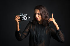 Thinking brunette woman looking at  vintage camera Royalty Free Stock Photo