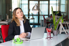 Thinking Business Lady in official clothing sitting at Office Table. Thinking charismatic Business Lady in official clothing black Jacket and white Shirt sitting Stock Photography