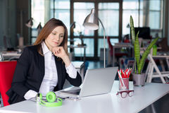 Thinking Business Lady in official clothing sitting at Office Table Royalty Free Stock Images