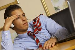 Thinking business man. Young business man is looking at his laptop Royalty Free Stock Photography
