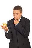 Thinking business man holding piggy bank Stock Photography