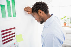 Thinking business man in the office leaning against the wall Stock Photos