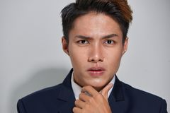 Thinking about business. Thoughtful young man in formalwear looking at camera while holding hand on chin and standing against grey. Background stock images