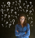 Thinking business woman with chalk question marks Stock Photo
