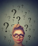Thinking business woman with glasses looking up at many questions marks above head Stock Images
