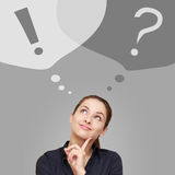 Thinking business woman looking up on question and exclamation signs Stock Image