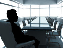 Thinking businessman. Silhouette businessman at the table in the empty conference hall Royalty Free Stock Photos