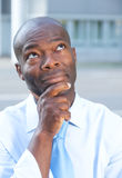 Thinking businessman from africa in front of his office Stock Image