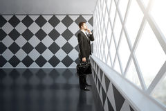 Thinking businessman in chessboard interior Stock Images