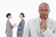 Thinking businessman with colleagues behind him Stock Photography