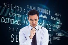 Thinking businessman holding glasses Stock Image
