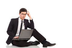 Thinking businessman with laptop. Royalty Free Stock Photos