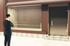 Thinking businessman looking at storefront. Thinking businessman looking at empty clean storefront in daylight. Side view, Mock up, 3D Rendering Royalty Free Stock Photography