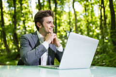 Free Thinking Businessman Sitting At The Office Desk Work At Laptop Computer In Green Forest Park. Freelancer With Hands On Chin Workin Stock Image - 97969871