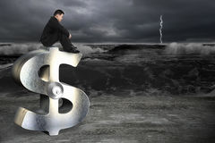 Thinking businessman sitting on silver dollar sign with lock Stock Images