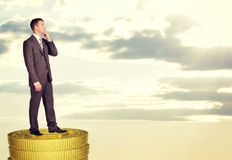 Thinking businessman standing on coins stack Stock Photography