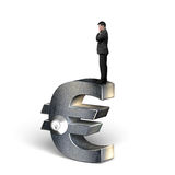 Thinking businessman standing on silver Euro symbol with lock Stock Image