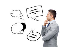 Thinking businessman in suit making decision. Business, people, communication and information concept - thinking businessman in suit with text bubble doodles Royalty Free Stock Photography