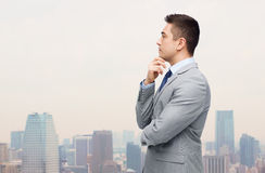 Thinking businessman in suit making decision. Business and people concept - thinking businessman in suit making decision over city background Royalty Free Stock Image