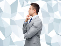 Thinking businessman in suit making decision. Business and people concept - thinking businessman in suit making decision over gray graphic low poly background Royalty Free Stock Images