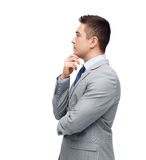 Thinking businessman in suit making decision. Business, people and office concept - thinking businessman in suit making decision Royalty Free Stock Photo